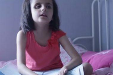 Domitille, petite fille aveugle, dans sa chambre, lit en braille
