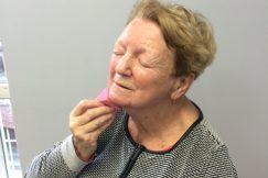 Une personne aveugle s'applique du fond de teint lors d'un cours de maquillage