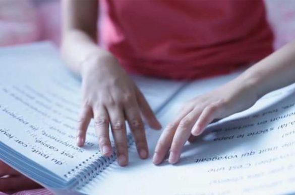 Zoom sur les mains de Domitille, qui lit en braille
