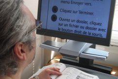 Un homme utilise un télé agrandisseur pour lire en gros caractères un document