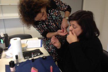 Une personne malvoyante se fait aider dans le maquillage de sa bouche