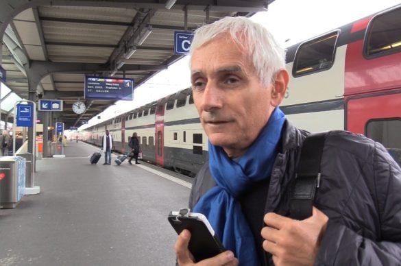 Pierre, déficient visuel, sur le quai d'une gare avec son smarthphone