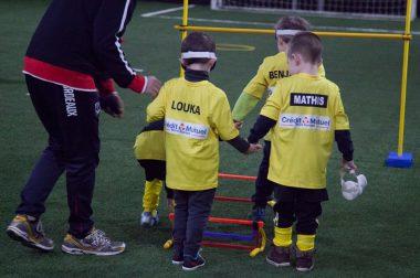 Les enfants joueurs de foot se déplacent lors d'une sensibilisation au cécifoot