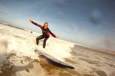 Claudy Robin debout bras écarté, genoux pliés prend une vague sur l'océan.