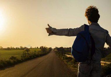 Jean-Pierre Brouillad qui fait du stop par un coucher de soleil.