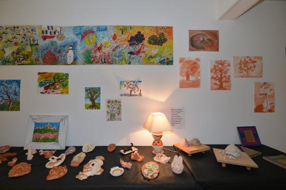 Poterie sur une table, petite lampe éclairée et tableaux éclairés au mur.