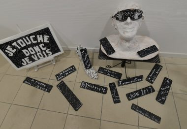 Sculpture d'un buste en papier maché blanc et lunettes noires.