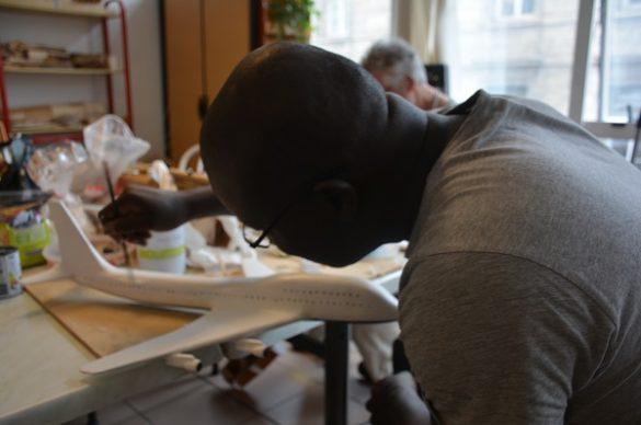 Un bénéficiaire travaille sur la maquette de son Boeing 747.