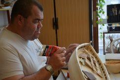 Un bénéficiaire tient une maquette de bateau en bois entre les mains et met une sorte de colle dessus pour combler les petits défauts.