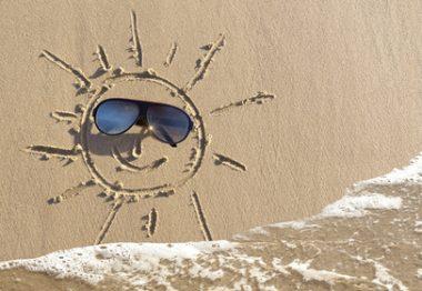 Soleil déssiné sur le sable avec lunettes à la place des yeux.