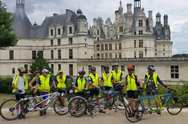 Le groupe de cyclistes en tandem voyant et non-voyants posent devant le château de Chambord