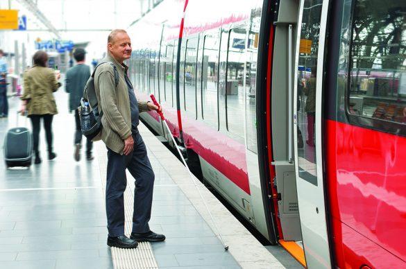Déficient visuel avec sa canne prêt à monter dans le train.