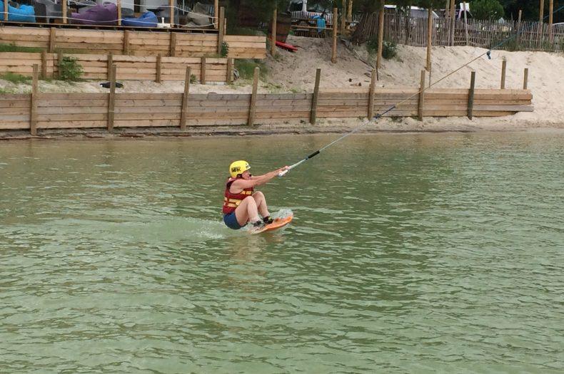Casque jaune, planche au pied, le sportif tiend le palonnier et sort de l'eau.