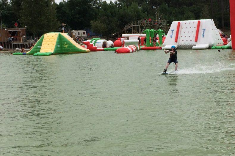 Un wakeboarder se fait tirer et glisse sur l'eau