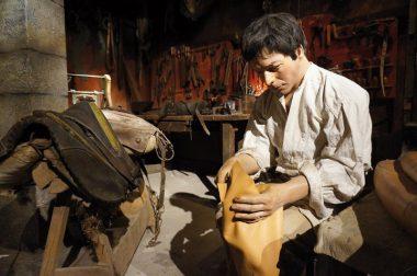 Un cordonnier comme en 1900 qui travaille sur du cuir