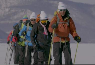 Les membres du groupe à la queue leu leu sur les skis sur le lac.