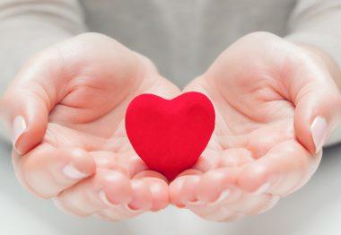 Un petit coeur rouge dans des mains d'une personne