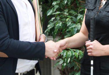 Un entrepreneur sert la main d'une non-voyante