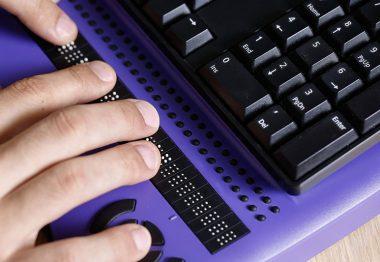 Zoom sur des mains et le clavier avec une plage braille