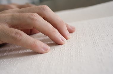 Des doigts parcourent une page en braille