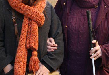 Une personne aveugle avec une canne tient le bras de son auxiliaire de vie sociale