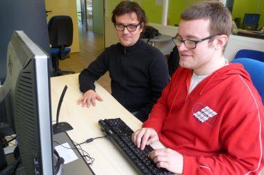Un élève est formé sur ordinateur avec un professeur