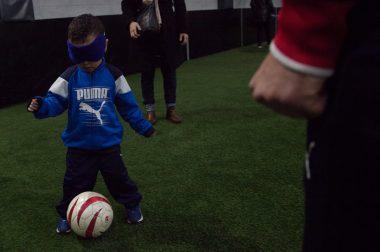 Un petit joueur de foot se déplace avec un ballon les yeux bandés