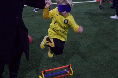 Un enfant saute un obstacle lors d'une sensibilisation au cécifoot