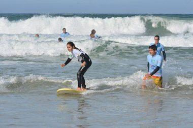 Jeune fille surfe debout sur la planche