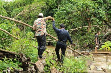Jean-Pierre Brouillaud donne la main à un Cambodgien qui comme lui arpente un tronc au bord de la rivière.