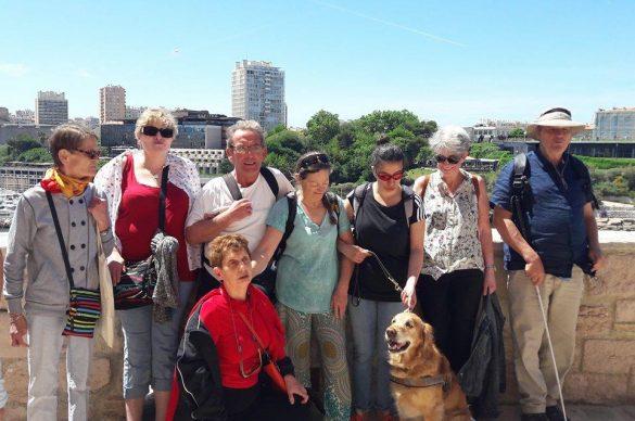 Groupes de bénéficiaires apputé sur une murette avec la ville en fond et le chien au premier plan.