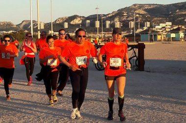 Course en binome de bénéficiaires portant tous un t-shirt orange pendant la Nocturne de Marseille