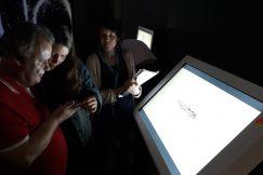 Des bénéficiaires essaient à l'aide d'un smartphone de répondre à une question posée sur un écran dans une pièce sombre.