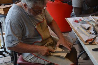 Jacques Vogel assis lime un morece de bois destiné à un bateau.