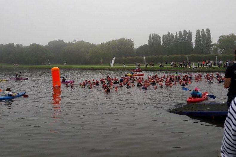 Les athlètes nagent dans l'eau grise du canal.