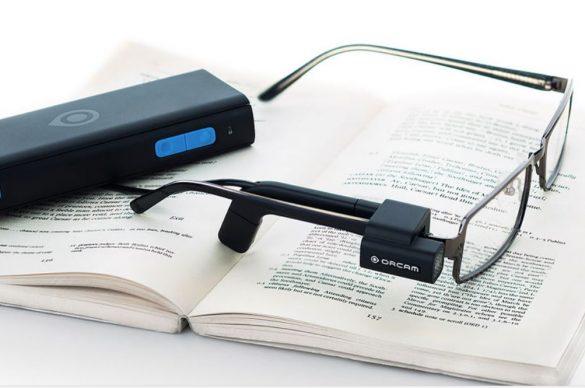 Le dispositif de vision artificielle MyEye® de Orcam posé sur un livre, avec les lunettes et le boîtier relié