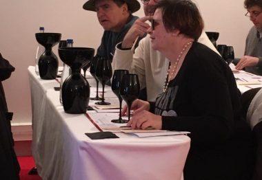 Verres noirs, carafes noires, table blanche et bénéficiaires assis derrière.