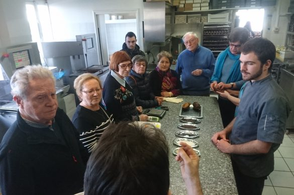 groupe de personnes autour d'une table de cuisine professionnelle.