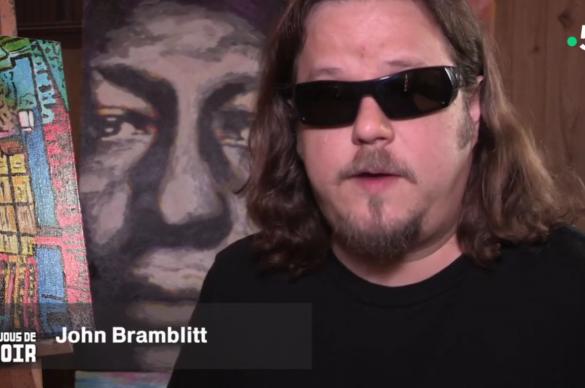 John Bramblitt avec des lunettes noires devant un portrait