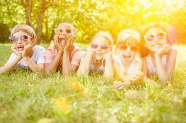 enfants allongés dans l'herbe avec lunettes de soleil.