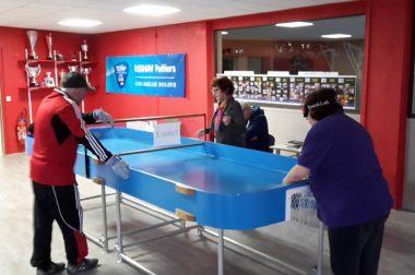 table de ping pong aux bords relevés dame qui joue avec une sorte de raquette.