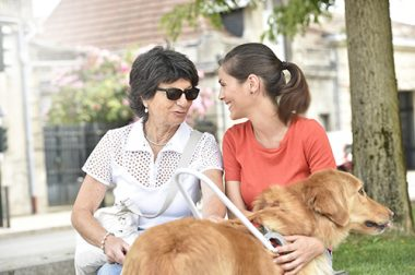 Une auxiliaire de vie assise sur un banc avec une personne aveugle accompagnée de son chien-guide