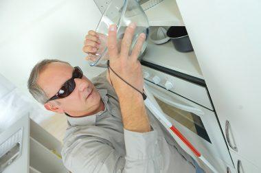 Une personne aveugle attrape un bol dans sa cuisine