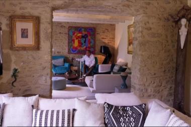 canapé, murs de pierre et tableau coloré