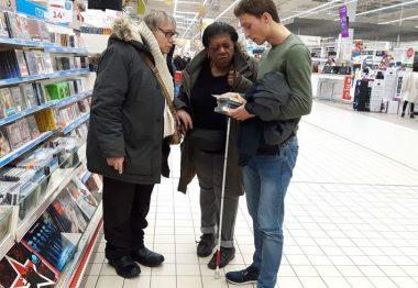 Damien auxiliaire de vie et un couple de malvoyants au rayon CD