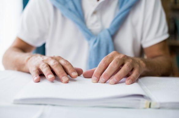 Un homme aveugle pose ses mains sur un livre transcrit en braille