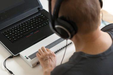 Un homme aveugle utilise une plage braille pour son ordinateur avec un casque sur la tête pour la synthèse vocale
