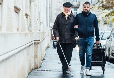 Florian, auxiliaire de vie, accompagne en ville Barthélémy-Michel, aveugle.