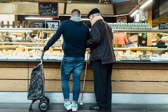 Un auxiliaire de vie accompagne un vieux monsieur aveugle devant un étal de fromages pour faire des courses