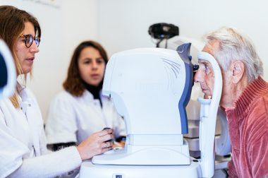 Une ophtalmologiste réalise des examens oculaires sur un patient dans le Bus du Glaucome de l'UNADEV, assistée de l'orthoptiste de l'UNADEV